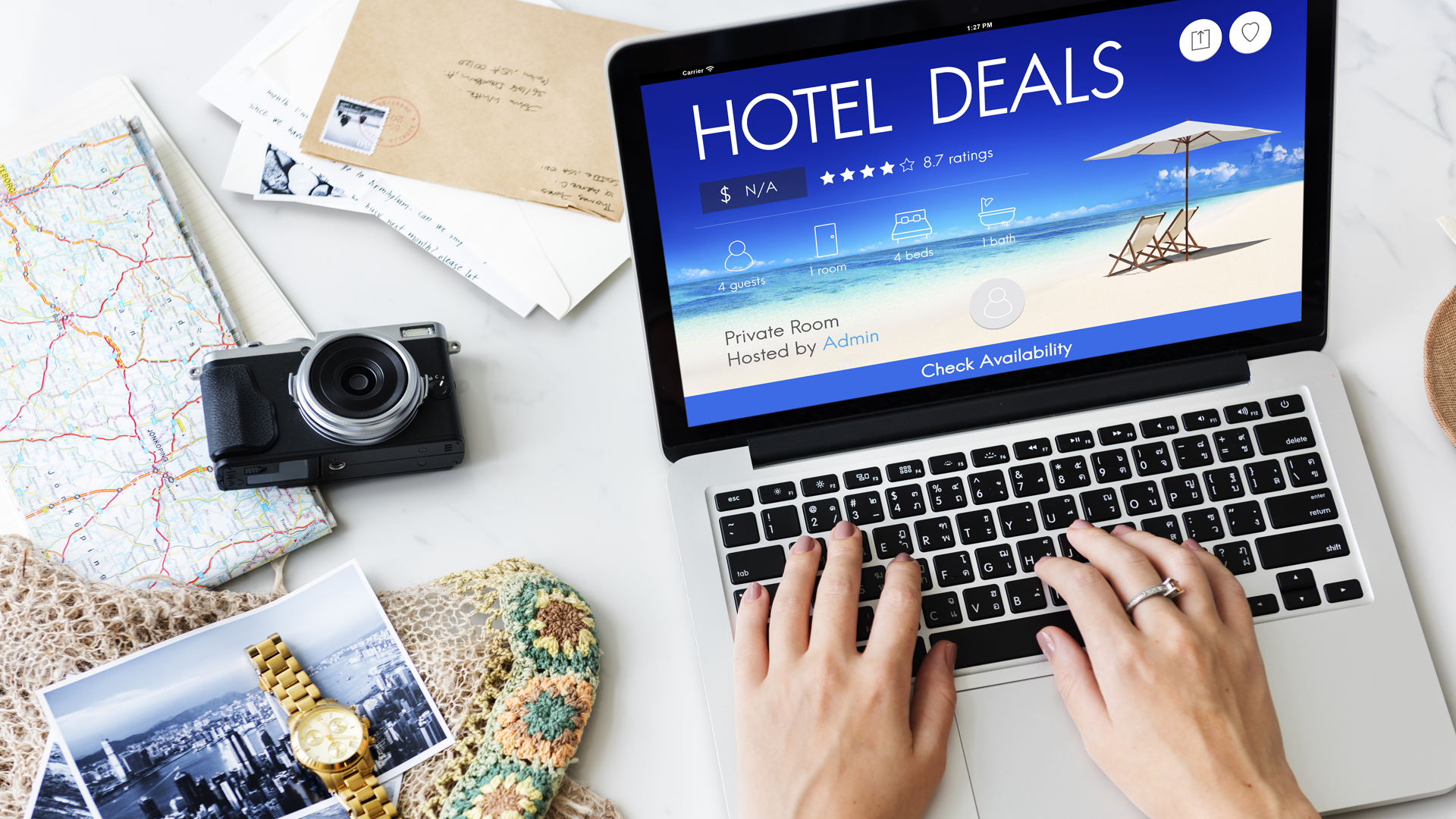 laptop with its screen showing Hotel Deals on a desk with a camera, maps, and travel plans