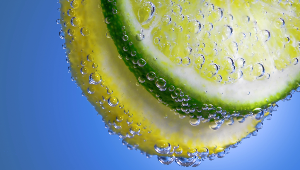 Seltzer bubbles tickle a green lime and yellow lemon