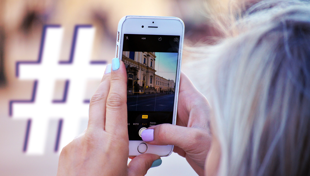 A woman takes a photo of an iconic tourist destination and uses an Instagram hashtag to achieve maximum visibility.